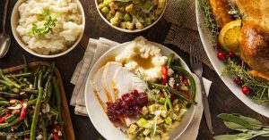 Photo of a holiday feast on a table with turkey. stuffing, mashed potatoes, gravey and green beans.