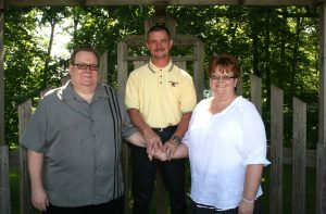 Photo of Rick Gardner standing in the center, with his hands uniting Paul and Debbie Oyler.