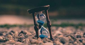 Photo of sand running through an hourglass.